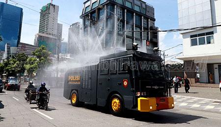 Polisi Semprotkan Disinfektan di Jalanan Surabaya